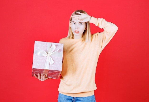 Jovem loira de jeans azul colocando a mão perto da testa enquanto segura a caixa de presente