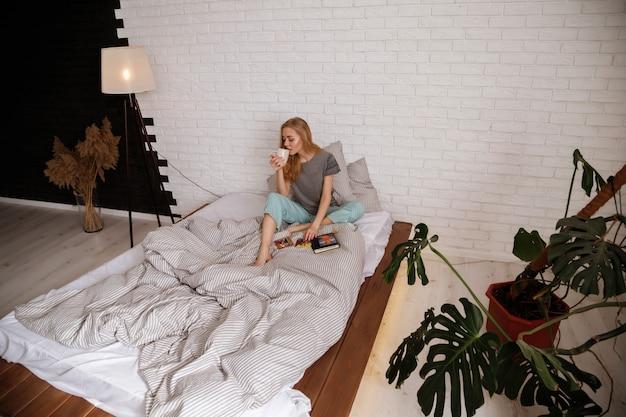 Jovem loira de pijama bebe café da manhã na cama. manhã preguiçosa em casa