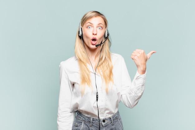 Jovem loira de telemarketing parecendo surpresa em descrença, apontando para um objeto ao lado e dizendo uau, inacreditável