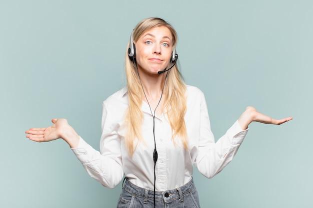 Jovem loira de telemarketing se sentindo intrigada e confusa, duvidando, ponderando ou escolhendo opções diferentes com expressão engraçada
