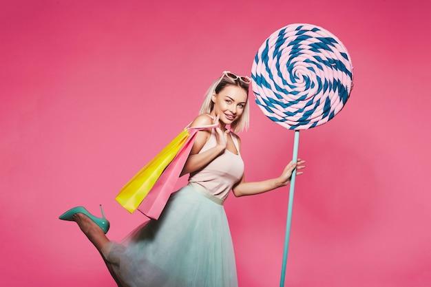 Jovem loira de top e saia em pé com enormes pirulitos doces e segurando sacolas de compras coloridas