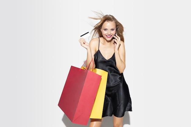 Jovem loira de vestido preto comprando na parede branca