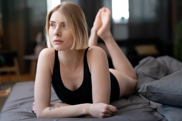 Jovem loira deitada na cama, ela descansando no quarto e pensando em algo
