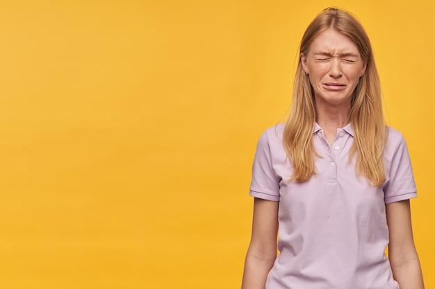 Jovem loira deprimida e chateada com sardas em uma camiseta lavanda em pé e chorando sobre a parede amarela.
