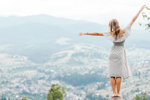 Jovem loira descalça linda com cabelos longos em vestido de verão em pé no topo da montanha conquistada