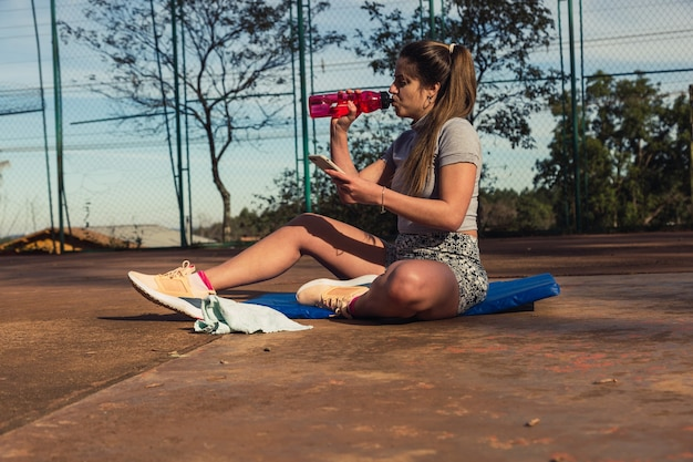 Jovem loira desportista bebendo água