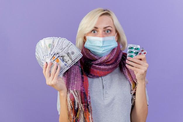 Jovem loira doente chocada com máscara médica e lenço segurando dinheiro e pacotes de comprimidos médicos isolados na parede roxa