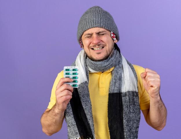 Jovem loira doente eslava com dores e colocando pacotes de pílulas médicas sob o chapéu de inverno e usando lenço segurando pacote de pílulas médicas com o punho fechado na parede roxa