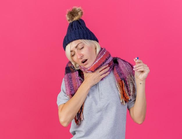 Jovem loira doente eslava insatisfeita com chapéu e lenço de inverno coloca a mão no pescoço e segura comprimidos médicos isolados na parede rosa com espaço de cópia
