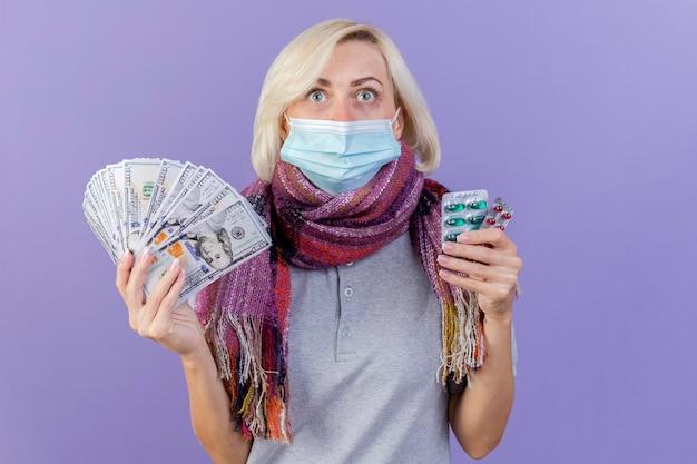 Jovem loira doente, impressionada, usando máscara médica e lenço segurando dinheiro e pacotes de comprimidos médicos isolados na parede roxa
