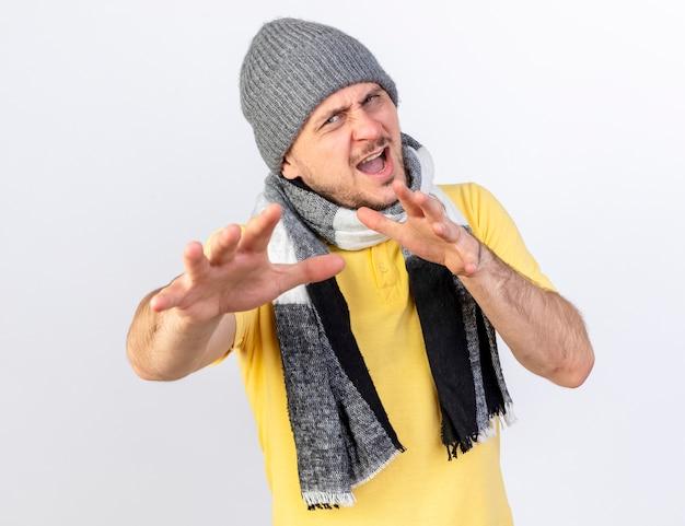 Jovem loira doente, irritada, usando chapéu de inverno e cachecol, estendendo as mãos, olhando para a frente, isolado na parede branca