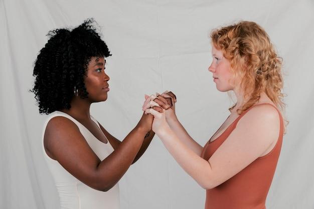 Jovem loira e africana em pé frente a frente, segurando as mãos uns dos outros