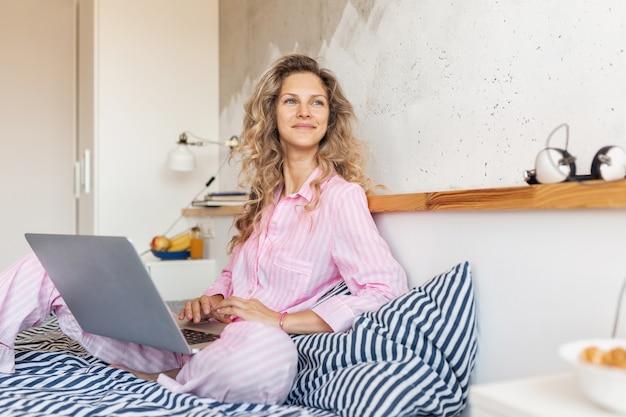 Jovem loira e bonita de pijama rosa, sentada na cama, trabalhando no laptop