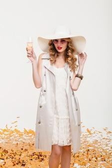 Jovem loira elegante com um grande chapéu e óculos escuros segurando uma taça de champanhe