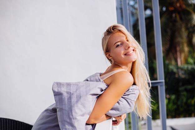 Jovem loira elegante europeia em cobertor na varanda tropical encontra o nascer do sol da manhã.