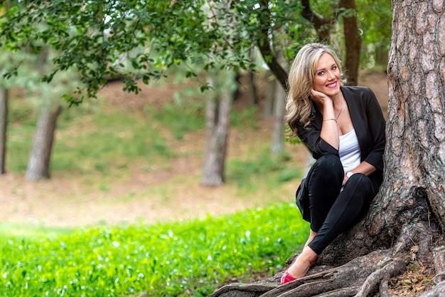 Jovem loira elegante sentada na floresta perto da árvore curtindo o silêncio