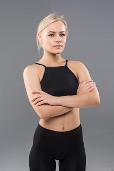 Jovem loira em forma de garota esportiva com roupas esportivas pretas demonstrando alongamento de corpo forte e musculoso