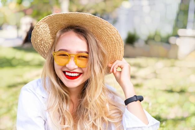 Jovem loira em óculos de sol amarelos, batom vermelho e chapéu de palha está sorrindo amplamente contra a grama verde no parque. conceito de vibrações positivas de verão, estilo de vida moderno, tempo de sol, close-up