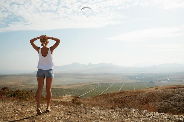 Jovem loira em pé no topo de uma colina