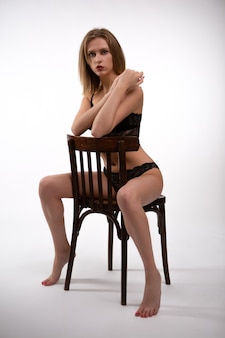 Jovem loira em roupa íntima de renda preta, sentada em uma cadeira de madeira