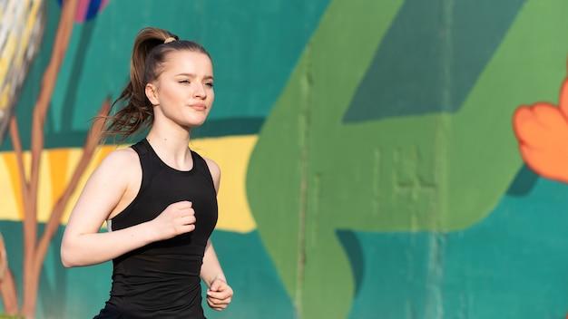 Jovem loira em roupas esportivas correndo na estrada em treinamento ao ar livre, parede multicolorida ao fundo
