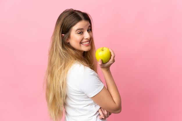 Jovem loira em um fundo isolado comendo uma maçã
