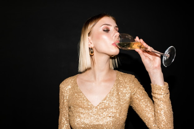 Jovem loira em um vestido elegante bebendo champanhe após um brinde em uma festa em uma boate onde algum acontecimento da vida está sendo celebrado