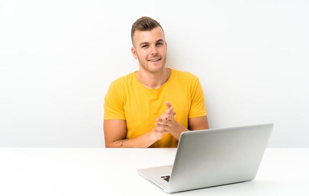 Jovem loira em uma mesa com um laptop aplaudindo