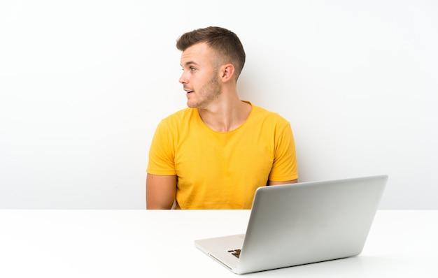 Jovem loira em uma mesa com um laptop, olhando para o lado