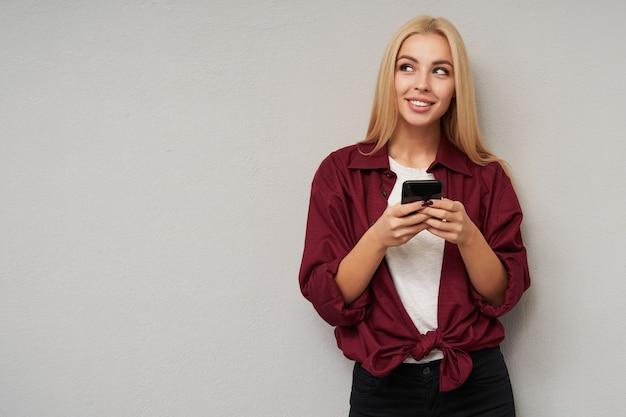Jovem loira encantadora com cabelo comprido, vestindo uma camisa cor de vinho e uma camiseta branca, em pé sobre um cinza claro, segurando o telefone celular com as mãos levantadas e olhando para o lado com um sorriso gentil