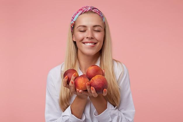 Jovem loira encantadora de olhos fechados, sorrindo amplamente e mordendo o lábio, segurando pêssegos e posando, vestindo roupas casuais