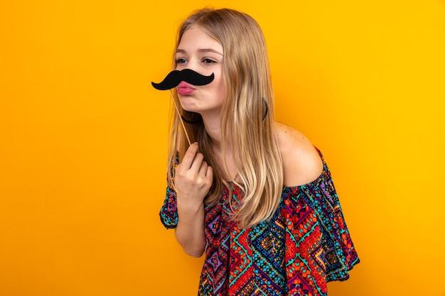 Jovem loira engraçada com bigode falso na vara olhando para o lado