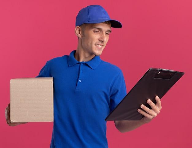 Jovem loira entregadora satisfeita segurando a caixa de papelão e olhando para a prancheta