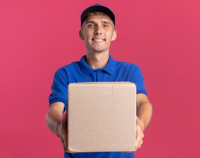 jovem loira entregadora sorridente segurando uma caixa de papelão