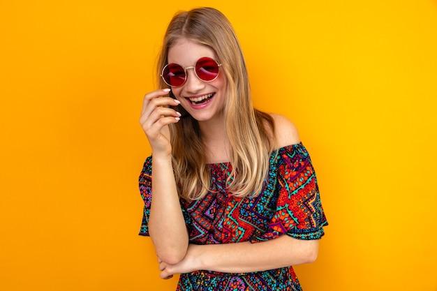 Jovem loira eslava rindo com óculos de sol olhando para frente