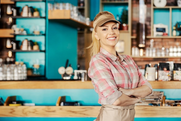 Jovem loira está em um café em frente ao bar e usa uma camisa xadrez e avental
