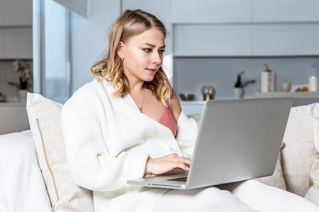 Jovem loira está sentada em um sofá com um laptop em uma grande e bem iluminada sala de estar. trabalho remoto e educação a distância.