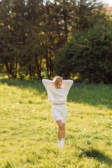 Jovem loira está vestindo um moletom branco, sorrindo e andando na floresta