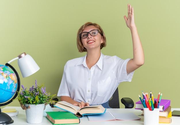 Jovem loira estudante sorridente de óculos, sentada na mesa com as ferramentas da escola, segurando o livro aberto, olhando para o lado, levantando a mão