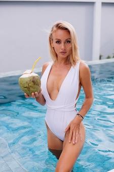 Jovem loira europeia em forma de mulher em maiô branco fica em azul claro piscina luz natural do dia segura palha de plástico de coco