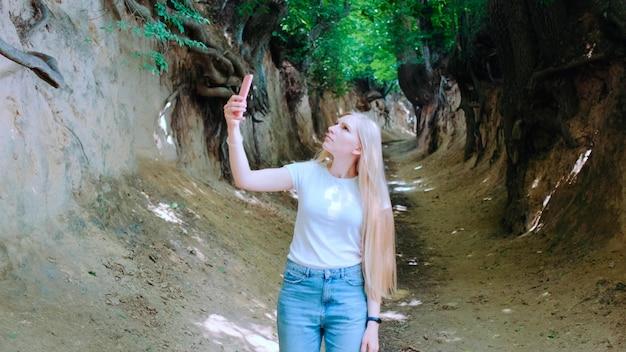 Jovem loira fazendo fotos em um smartphone no desfiladeiro mágico de raízes situado em kazimierz dolny em ...