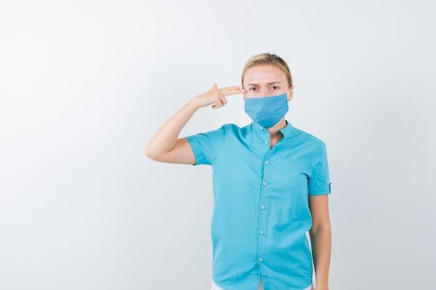 Jovem loira fazendo gesto de suicídio com roupas casuais, máscara e parecendo deprimida