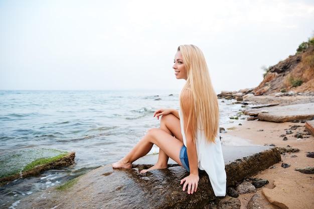Jovem loira feliz com cabelo comprido sorrindo na praia