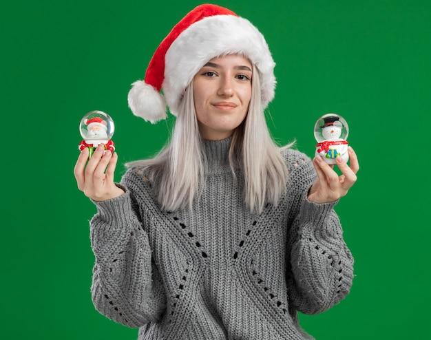 Jovem loira feliz com suéter de inverno e chapéu de papai noel segurando globos de neve de brinquedo de natal, olhando para a câmera, sorrindo alegremente em pé sobre um fundo verde