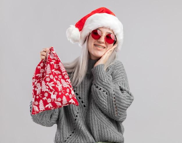 Jovem loira feliz com suéter de inverno e chapéu de papai noel segurando uma sacola vermelha de papai noel com presentes de natal sorrindo alegremente em pé sobre a parede branca