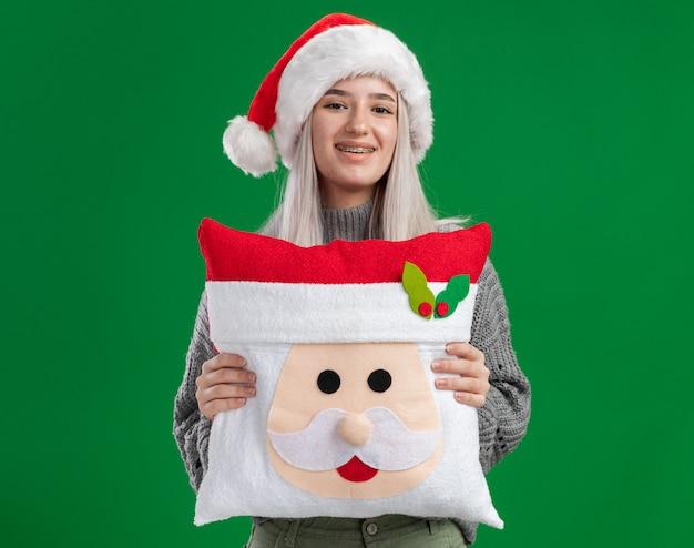 Jovem loira feliz com um suéter de inverno e um chapéu de papai noel segurando uma almofada de natal, olhando para a câmera com um sorriso no rosto, de pé sobre um fundo verde