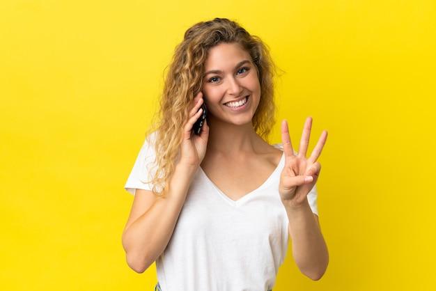 Jovem loira feliz usando telefone celular isolado em um fundo amarelo e contando três com os dedos