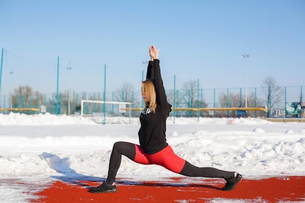 Jovem loira fêmea caucasiana em caneleiras violetas, esticando o exercício em uma pista de corrida vermelha em um estádio de neve. estilo de vida em forma e esportes