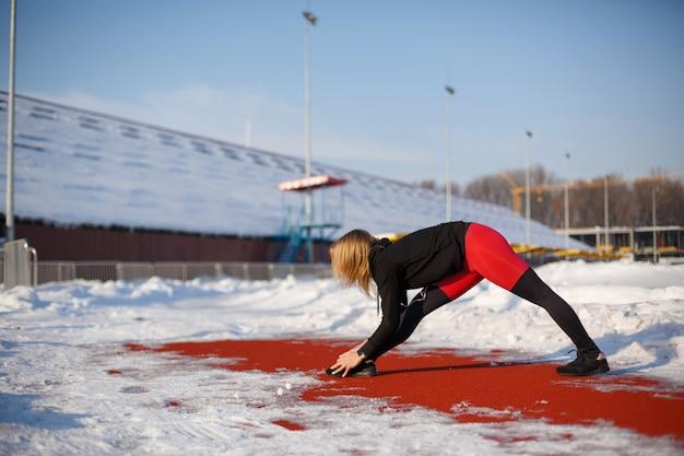 Jovem loira feminina caucasiana em caneleiras vermelhas, esticando o exercício em uma pista de corrida vermelha em um estádio de neve