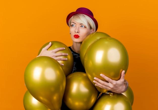 Jovem loira festeira carrancuda usando chapéu de festa em pé atrás de balões, agarrando-os olhando para o lado isolado em fundo laranja